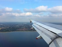 View from plane window over England. Wing flaps lower in readiness for landing at Heathrow Airport, as plane flies over the Queen Victoria Reservoir, England, UK Stock Photo