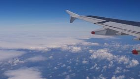 View from a plane window: a plane wing over clouds and blue sky stock video footage