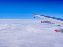 View from a plane window: a plane wing over clouds and blue sky Royalty Free Stock Photography