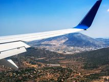 View of plane wing against mountains, hills and valleys of Greece royalty free stock images