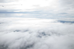 View from a plane wing window. View of jet plane wing with cloud patterns Royalty Free Stock Images