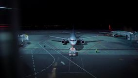 Illuminated aerodrome in night time with planes prepared for leaving