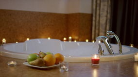 View of plate with fruits standing near jacuzzi in bathroom stock video footage