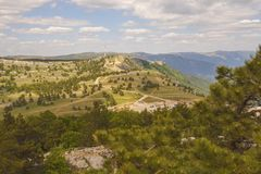 View of the plateau of mount AI-Petri through the branches of coniferous trees growing on a hill. Crimea royalty free stock photos