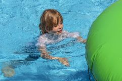View of a playing child in a swimming pool trying to swim to his inflatable animal. View of a cheerfully playing child in a swimming pool with blue water, trying stock image