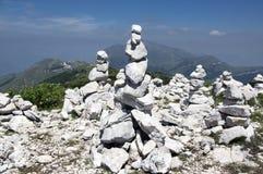 View point with white stone cairns on hiking trail Alta Via del Monte Baldo, ridge way in Garda Mountains. Mountain edge, harmony and balance royalty free stock image