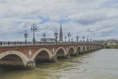 Pont de Pierre and Basilica of St. Michael with its tower under clouds, in Bordeaux, France royalty free stock photo
