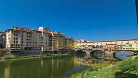View on The Ponte Vecchio on a sunny day timelapse hyperlapse, a medieval stone segmental arch bridge over the Arno. River, in Florence, Italy, noted for still stock footage