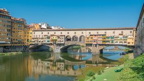 View on The Ponte Vecchio on a sunny day timelapse, a medieval stone segmental arch bridge over the Arno River, in. Florence, Italy, noted for still having stock footage