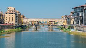 View on The Ponte Vecchio on a sunny day timelapse, a medieval stone segmental arch bridge over the Arno River, in. Florence, Italy, noted for still having stock video footage
