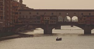 The view of Ponte Vecchio at sunset. The view of Ponte Vecchio, the famous Arno river bridge from Uffizi Gallery. Also known as `Old Bridge`, it is one of the stock footage