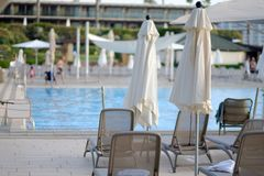View pool bed, beach chair with umbrellas chaise lounges near the pool. Plank beds for suntan at hotel standing with umbrellas chaise lounges near the pool royalty free stock photo
