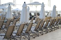 View pool bed, beach chair with umbrellas chaise lounges near the pool. Plank beds for suntan at hotel standing with umbrellas chaise lounges near the pool stock images