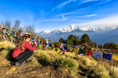 View from Poon hill. Young tourist taking photos at Poon hill in Nepal royalty free stock image