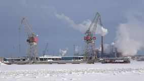 View of the port cranes and Smoking pulp and paper mill `Sunila`, February day. Kotka, Finland. KOTKA, FINLAND - FEBRUARY 25, 2018: View of the port cranes and stock video