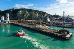Napier Port, Hawke`s Bay, New Zealand. A view of the Port of Napier from high up on a cruise ship. A tugboat can be seen returning to its berth. Logging and stock photo