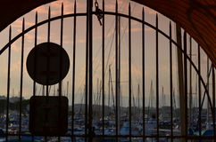 View on port of yacht through a metal gate Stock Photos