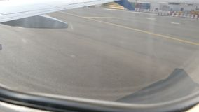 View from porthole of the plane to the runway. The plane is preparing for takeoff stock footage