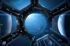 View from a porthole of space station on the Earth background. Stock Images