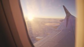 View through the portholes of the plane to the setting sun and the sky stock video footage