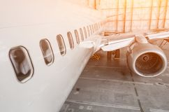 View of the portholes, wing and engine of the aircraft for maintenance in the hangar. Stock Photography