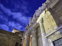 Portico d`Ottavia at night. View of Portico d`Ottavia at night, from below looking the sky with clouds and stars. The colonnaded walks of the portico enclosed royalty free stock image