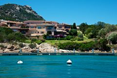 View of Porto Cervo`s luxury villa with private marina. In front of the blue sea Royalty Free Stock Images