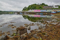 View of Portree harbor with reflections and colorful houses, seen from the seashore, Isle of Skye, Highlands, Scotland, UK Royalty Free Stock Photos