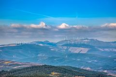 View of a portuguese landscape, wind turbines on top of mountains and dramatic sky as background. Portugal clouds cloudy valley environment electricity mill stock images
