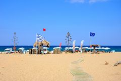 View of Potamos beach, Malia. View of Potamos beach with flags and parasols and the sea to the rear, Malia, Crete, Greece, Europe Royalty Free Stock Image