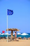 View of Potamos beach, Malia. Woman standing under a parasol on Potamos beach with a European Union flag in the foreground, Malia, Crete, Greece, Europe Stock Images