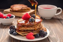 Pouring honey on Pancakes with blueberries and strawberries and cup of red juice. View of a Pouring honey on Pancakes with blueberries and strawberries and cup stock photos