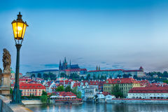 View of Prague Castle, mala Strana and Vltava river in Prague from Charles Bridge with street lamp during blue hour sunrise Royalty Free Stock Photos
