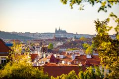 View of Prague Castle over red roof from Vysehrad area at sunset lights, Prague, Czech Republic. View of Prague Castle over red roof from Vysehrad area at sunset stock photo