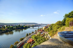 View on Prague cityscape and Vltava river in late afternoon sun with an old metallic map of Prague landmarks sculpture. In the foreground Royalty Free Stock Photo