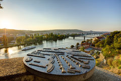 View on Prague cityscape and Vltava river in late afternoon sun with an old metallic map of Prague landmarks sculpture. In the foreground Stock Photos