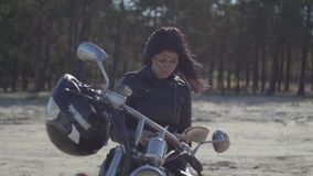 View of the pretty caucasian girl in a black leather jacket sitting on the motorcycle reading book. Hobby. View of the pretty caucasian girl sitting on the stock footage