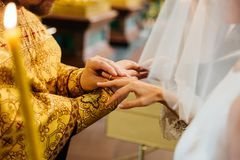 View of priest put on ring on hand of brides hand, pose in Christian church during wedding ceremony, burning candle in foreground stock photos