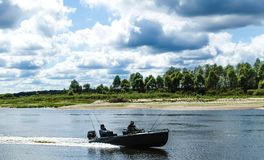 The fishermen move in a motor boat through the River royalty free stock photo