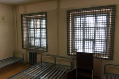 View of the prison cell from the inside. Lattices on the windows and iron beds Stock Photo