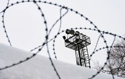 View on prison guarding tower through barbed wire. View on a prison guarding tower through barbed wire stock photo