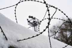 View on prison guarding tower through barbed wire. View on a prison guarding tower through barbed wire stock photography