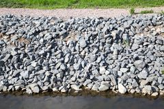 View of the protection of the coast of gray granite stones. stock photography
