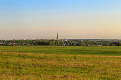 View of the provincial Russian town with hills in the spring. The house in the green, bell tower on the horizon Stock Photos