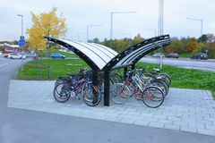 View of public parking place for bicycles with roof protection. City concept. Urban concept. Sweden, Uppsala, 17-10-2017 stock photography