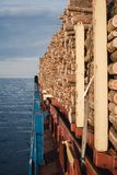 Wood carried by ship on deck.Ship sailing at sea. stock images