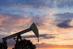View of pumpjack pumping oil at sunset Royalty Free Stock Images