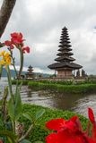 Pura Ulun Danu temple on a lake Beratan on cloudy day with green grass and colorful flowers foreground at Bali, Indonesia. View of Pura Ulun Danu temple on a royalty free stock images