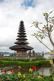 Pura Ulun Danu temple on a lake Beratan on cloudy day with green grass and colorful flowers foreground at Bali, Indonesia. View of Pura Ulun Danu temple on a royalty free stock photography