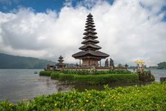 Pura Ulun Danu temple on a lake Beratan on cloudy day with green grass and yellow flowers foreground at Bali, Indonesia. View of Pura Ulun Danu temple on a lake royalty free stock image